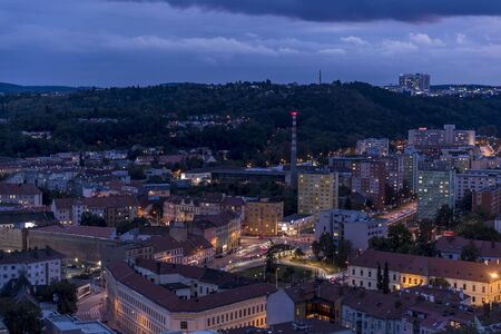 Crossing during late day to night timelapse to Mendel Square in Brno with cars and public transport, trams and buses passing through busy square and the surrounding streets which slowly light up. Stock fotó