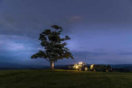 At night abandoned tree on hill at dark sunset with rising moon in full moon over horizon between nature and landscape overlooking dark moody clouds and tractor carrying stacks of straw at night.