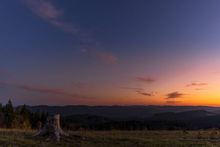 Colorful time-lapse sunset with old abandoned tree trunk and main subject colorful sky with orange and blue colors sunset captured in high mountains Beskydy area Czech Republic. Stok Fotoğraf