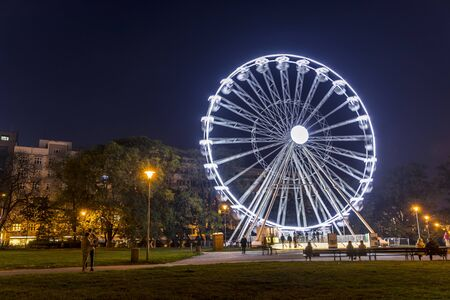 Huge Christmas illuminated wheel for people with a beautiful view of Moravian Square in Brno moving during a cold evening during the time lapse video dominates the Christmas preparations in city Banco de Imagens