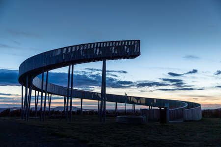 Kobyli lookout point A wooden spiral construction in the South Moravia region during sunset with moving clouds and views of the exuberant farms and fields.