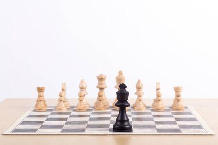Zbliżenie na szachownicę ze wszystkimi białymi figurami w pozycji początkowej i czarnym królem stojącym samotnie