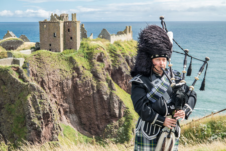 Traditional Scottish bagpiper in full dresscode at Dunnottar Castle in Stonehaven
