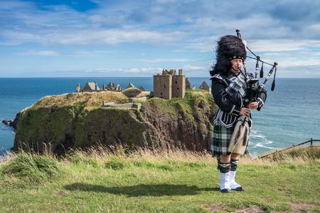 highlander: Gaitero escocés tradicional en plena regla de etiqueta en el castillo de Dunnottar en Stonehaven Foto de archivo