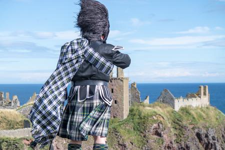 dunnottar castle: Traditional Scottish bagpiper in full dresscode at Dunnottar Castle in Stonehaven