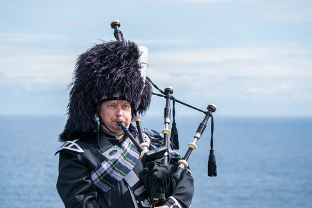 Traditional Scottish bagpiper in full dress code at the sea Stock Photo
