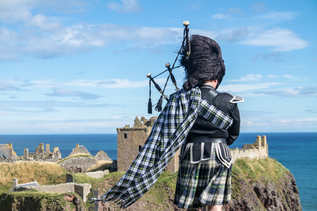 scot: Traditional Scottish bagpiper in full dresscode at Dunnottar Castle in Stonehaven