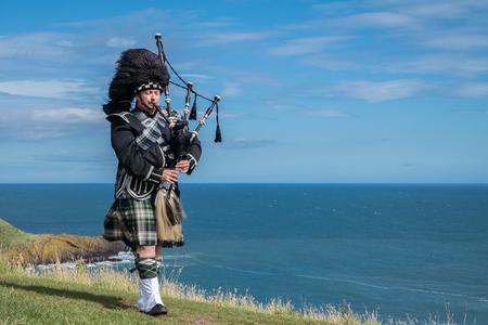 스톤 헤븐의 Dunnottar Castle에서 전체 드레스 코드로 전통적인 스코틀랜드 백파이프 스톡 콘텐츠