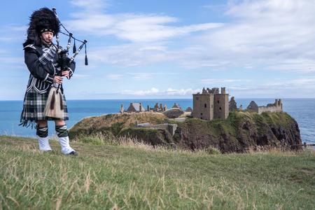 ストーンヘブンにダノター城で完全 dresscode で伝統的なスコットランド笛 写真素材