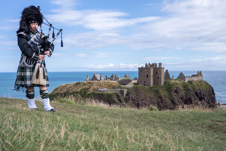 castle: Traditional Scottish bagpiper in full dresscode at Dunnottar Castle in Stonehaven