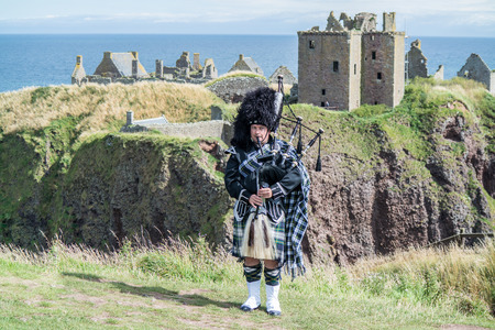 dresscode: Traditional Scottish bagpiper in full dresscode at Dunnottar Castle in Stonehaven