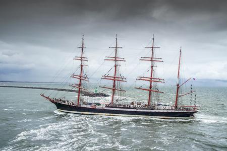 ijmuiden: Ijmuiden, Netherland - August 18 2015: Tall ship passing lighthouse in the rain storm