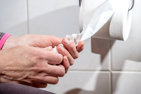 Close-up Of A ladys Hand Using Toilet Paper