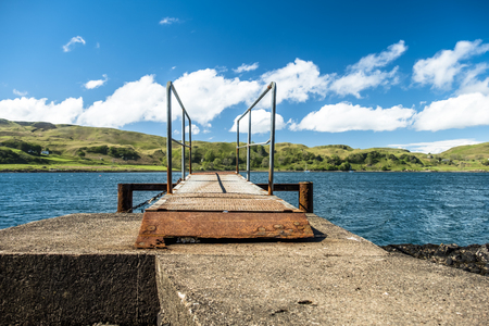 Rusty sea pier at the Atlantic with green Island