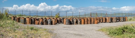 Rusty fuel and oil casks stored at an fence Stock Photo