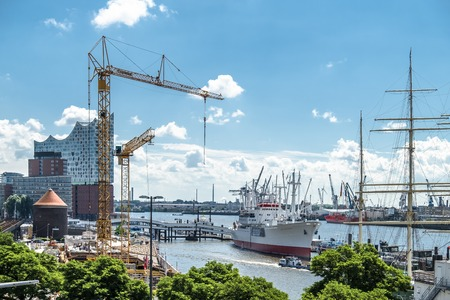 st: Hamburg  Germany - July 14, 2017: Cranes are working at the construction site between the St. Pauli Piers and Baumwall