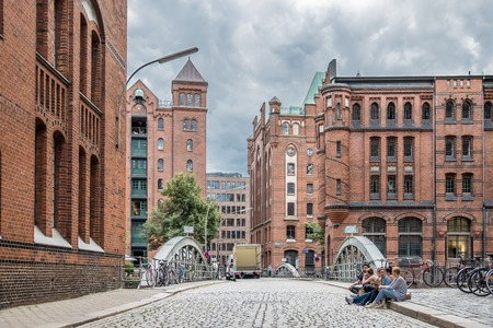 warehouse building: Hamburg  Germany - July 14, 2017: Young folks sitting in the streets of the famous Speicherstadt Editorial
