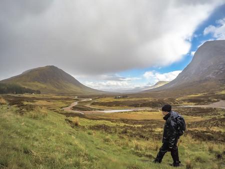highlander: Glencoe, Scotland - May 18 2017 : Man is hiking through the rain in Glencoe, Scotland