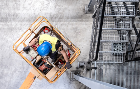 Aerial of a worker on a cherry picker Imagens