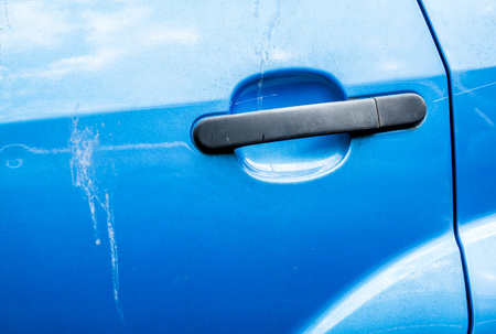Blue car door handle and scratched car paint with birds droppings Stock Photo