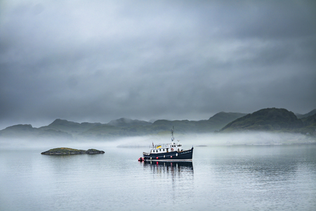 Alone boat driving through in the foggy sea in the scottish highlands