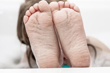 Closeup of wrinkeled feet on edge of bubble bathtub