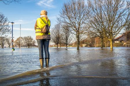 Lady standing in flooded street Standard-Bild