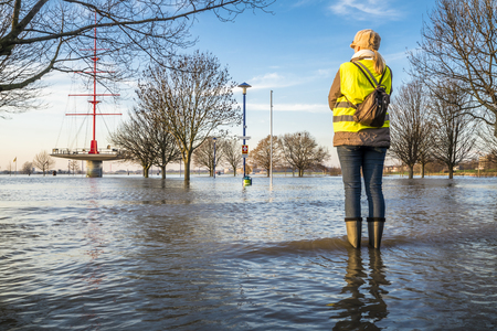 Lady standing in flooded street Banque d'images