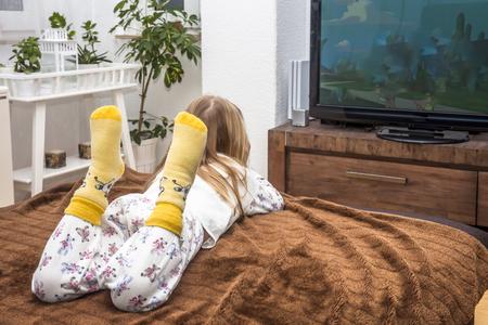 Niña mirando la televisión en el sofá Foto de archivo - 93469746