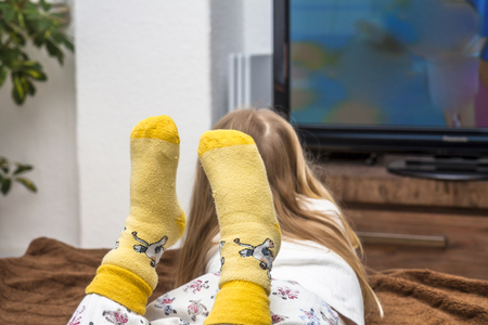 Little girl watching television on the sofa