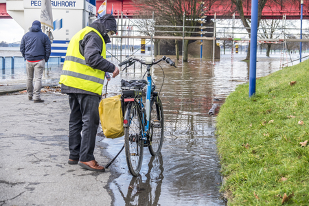 Duisburg , Germany - January 08 2017 : Bicycle driver surprised by the river Rhine flooding the promenade in Ruhrort Redakční