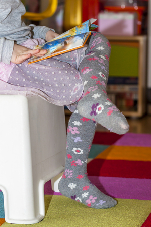 Little girl reading colourful book with pictures and text Banque d'images