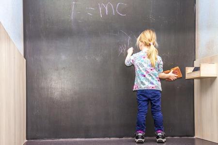 Jolie petite fille écrivant sur un tableau Banque d'images - 94673179