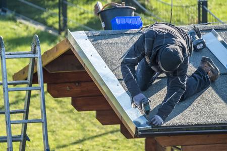 Roofer worker using battery-powered screw gun