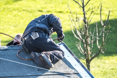 Roofer repairing the metal facing with tin after storm Standard-Bild