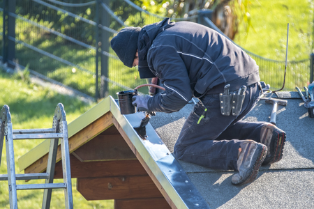Roofer repairing the metal facing by painting after storm Stock Photo