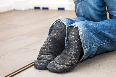 Man laying laminate in socks