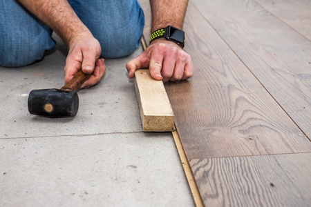 Man laying laminate by using hammer and wooden block