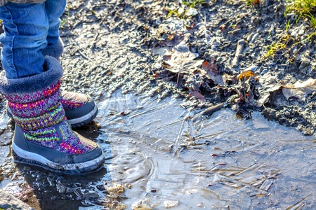 Child stands on icy dirty puddle Stock Photo