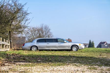 Moers / Duitsland - 09 februari 2018: Uitgetekende extra lange auto staat in het veld zonder kentekenplaat