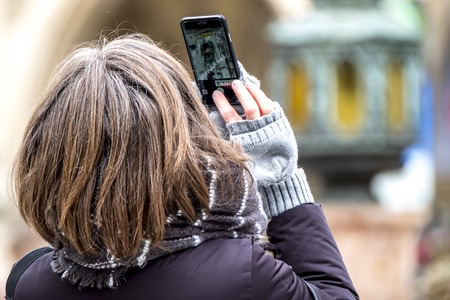 Lady photographing with smart phone with life picture of the historic town hall of Munich, Germany