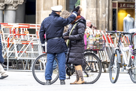 Munich / Germany - February 15 2018: Street warden arguing with bicycle driver