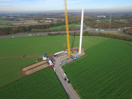 MOERS / GERMANY - November 03 2015 : Crane lifts the engine room on the wind power generator construction tower - Aerial view Редакционное