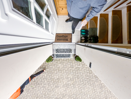 Postman is delivering the parcel to the customer dor - aerial view. Stock Photo