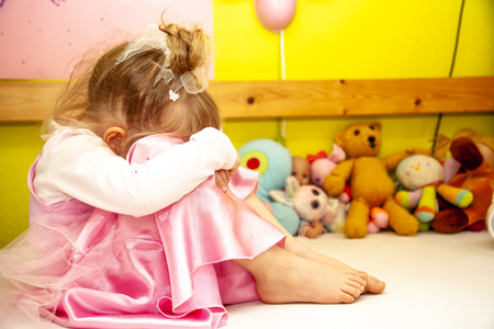 Cute little girl sitting on bed very unhappy.