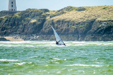 Wind surfer enjoys the beach at Newborough Warren with the Island of Llanddwyn in the background , Isle of Anglesey, North Wales, UK Stockfoto