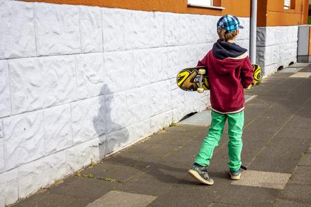 Young walking along white wall with longboard 版權商用圖片