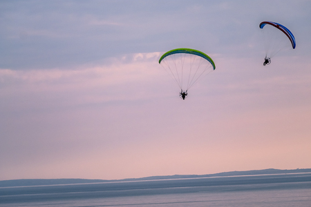 Paraglider flying with paramotor during sunset