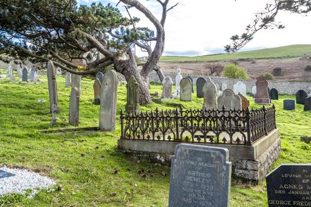 Llandudno / Wales, UK - April 22 2018 : Dramatic graves standing at St Tudnos church and cemetery on the Great Orme at Llandudno, Wales, UK