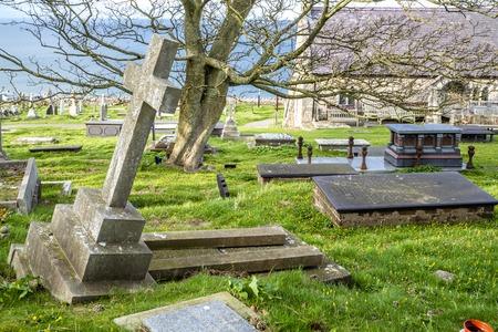 Llandudno  Wales, UK - April 22 2018 : Dramatic graves standing at St Tudnos church and cemetery on the Great Orme at Llandudno, Wales, UK